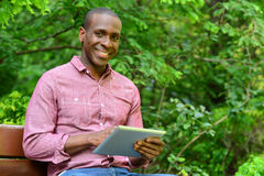 Happy guy using his tablet pc, outdoors Stock Photography