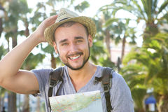 Happy guy on vacation with bag and hat holding map. Portrait of a happy guy on vacation with bag and hat holding map Stock Image