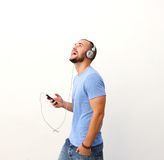 Happy guy walking with cell phone and headphones Stock Images
