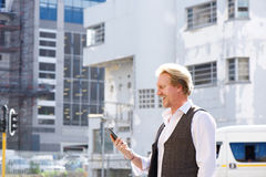 Happy guy walking outdoors in the city and looking at mobile phone Royalty Free Stock Photo