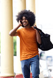 Happy guy walking in town with mobile phone and bag Stock Photos