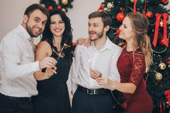 Happy guys and girls enjoying New Year party with Bengal lights. Portrait of happy guys and girls enjoying New Year party with Bengal lights royalty free stock images