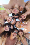 Happy guys and girls standing together in a circle. Low angle view of happy guys and girls standing together in a circle against blue sky Royalty Free Stock Images