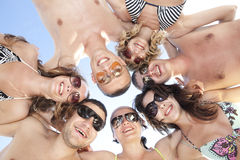 Happy guys and girls standing together in a circle. Low angle view of happy guys and girls standing together in a circle against blue sky Royalty Free Stock Photos