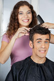 Happy Hairdresser Cutting Client's Hair At Salon Stock Images