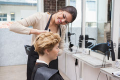 Happy hairdresser cutting a customers hair Stock Images