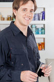 Happy hairdresser holding scissors Royalty Free Stock Images