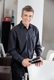 Happy Hairdresser Holding Straightener. Portrait of happy male hairdresser holding straightener at salon Stock Images