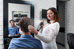 Happy hairstylist is making hairdo Royalty Free Stock Photos