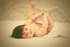 Happy baby girl lying on blanket at home royalty free stock photos