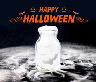 Happy halloween with bat fly in smoke in glass bottle on black b Stock Photography