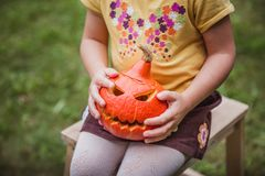 Happy Halloween. Beautiful smiling girl seats on wooden chair and holds little pumpkin Jack O Lanterns outdoors stock image
