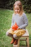 Happy Halloween. Beautiful smiling toddler seats on wooden chair and holds little pumpkin Jack O Lanterns outdoors royalty free stock images