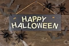 Happy Halloween sign with spiders and bats on old wood Stock Photos