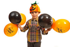 Happy Halloween boy. Happy kid with pumpkin hat holding  orange and black Halloween balloons isolated on white background Royalty Free Stock Image