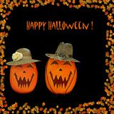 Happy Halloween Carved Pumpkins. Halloween Jack O Lanter couple wearing hats.  Colorful autumn leaves surround the pumpkins, isolated on black background with Royalty Free Stock Photo