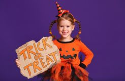 Happy Halloween! cheerful child girl in costume with pumpkins on Royalty Free Stock Photo