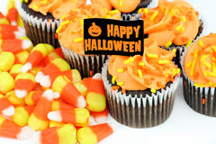 Happy Halloween cupcakes and candy corn on white. Orange iced chocolate cupcakes and candy corn with a Happy Halloween flag Stock Photo