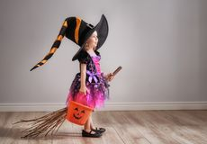 Child on Halloween. Happy Halloween! Cute little laughing girl in witch costume with a broomstick royalty free stock image