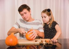 Happy halloween. Daughter and father carving pumpkin for Halloween stock photo