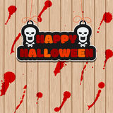 Happy Halloween decoration. Hanging sign with skulls on the background of wooden wall with red splashes. Royalty Free Stock Photography
