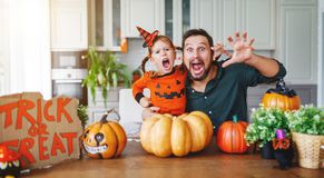 Happy Halloween! family father and child daughter getting ready. For holiday cutting a pumpkin royalty free stock photos