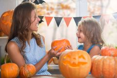 Happy Halloween. Family little beautiful girl with mother celebrating home with pumpkins stock images