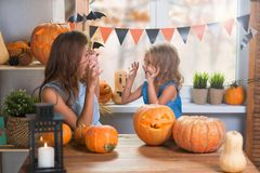 Happy Halloween. Family little beautiful girl with mother celebrating home  with pumpkins stock image