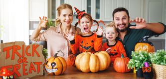 Happy Halloween! family mother father and children cut pumpkin f. Happy Halloween! family mother father and children cut a pumpkin for holiday home stock photography