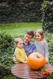 Happy halloween. Father and two daughters look at the face cut in the pumpkin for Halloween outside. stock photos