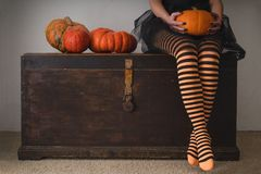 Happy halloween! Female feet in stockings with an orange pumpkin. Stock Image