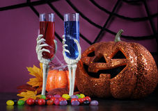 Happy Halloween ghoulish party cocktail drinks with skeleton glasses and pumpkin Stock Photography