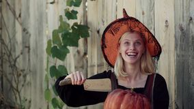 Happy Halloween girl. Beautiful young surprised woman in witch hat and Halloween costume holding pumpkin. Emotional stock video footage