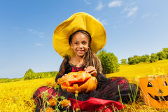 Happy Halloween girl sitting on yellow grass Royalty Free Stock Image