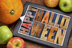 Happy Halloween greeting card. Text in vintage grunge wood type printing blocks on a digital tablet with a pumpkin and apples stock images