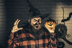 Happy Halloween. Halloween hipster with scary face in witch hat. And plaid shirt. Holiday celebration symbols on brick wall. Jack o lantern. Mystery and horror stock photo