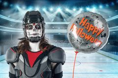 Happy halloween. hockey player in a hockey helmet and mask with a balloon against the backdrop or background of a hockey field. Al Stock Image