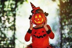 Happy Halloween! horrible creepy child girl in pumpkin costume Royalty Free Stock Images