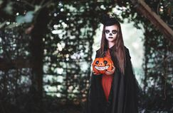Happy Halloween! horrible creepy child girl in witch costume wi. Th a pumpkin in forest royalty free stock photography