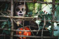 Happy Halloween! horrible creepy child girl in witch costume wi. Th a pumpkin in forest stock images