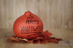 Happy Halloween inscription on the pumpkin with leaves Royalty Free Stock Image