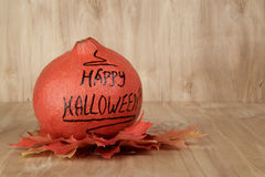 Happy Halloween inscription on the pumpkin with leaves Stock Images