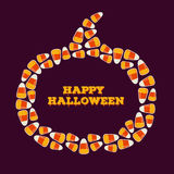 Happy Halloween inscription with pumpkin shaped frame made of small candy corns. Trick or treat concept greeting card Stock Image
