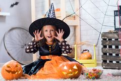 Happy Halloween. A little beautiful girl in a witch costume celebrates a home in an interior royalty free stock photo