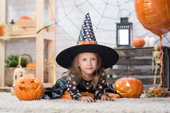 Happy Halloween. A little beautiful girl in a witch costume celebrates a home in an interior stock image