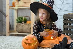 Happy Halloween. A little beautiful girl in a witch costume celebrates a home in an interior stock photography