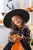 Happy Halloween. A little beautiful girl in a witch costume celebrates a home in an interior royalty free stock photography