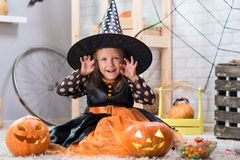 Happy Halloween. A little beautiful girl in a witch costume celebrates a home in an interior royalty free stock image
