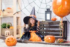 Happy Halloween. A little beautiful girl in a witch costume celebrates a home in an interior royalty free stock photos