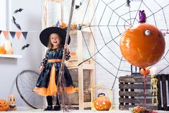 Happy Halloween. A little beautiful girl in a witch costume cele. Brates a home in an interior with pumpkins Stock Photos